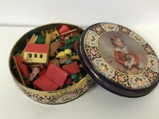 A tin with a collection of treen decorated farmyard animals, farm buildings, fences etc.