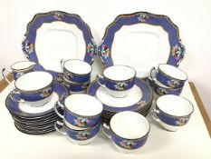 An Adderleys Suez pattern thirty one piece 1920s/30s fruit and blue and gold bordered tea set