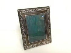 A modern silver Celtic style rectangular photograph frame with green velvet back (18cm x 14cm.
