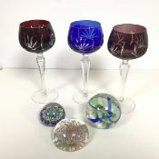 Three Bohemian style ruby, amethyst and blue slice cut hock glasses and three various paperweights