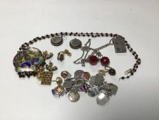 A mixed lot including an Indian enamelled pendant, a charm bracelet, a silver ingot on chain, a pair