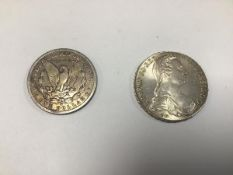 An Austrian white metal coin dated 1780 and an American silver dollar, dated 1886 (54.57g)