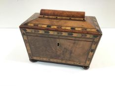 An early Victorian walnut tea caddy with Tunbridgeware banding, of sarcophagus form, raised on