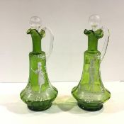 A pair of Mary Gregory style green glass ewers, with characteristic decoration in white enamel,