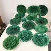 An assortment of green majolica plates with foliate decoration, some marked Wedgwood, two marked