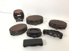 A collection of Chinese cherrywood carved stands, all with fretwork, one of barrel form (h.8cm x d.