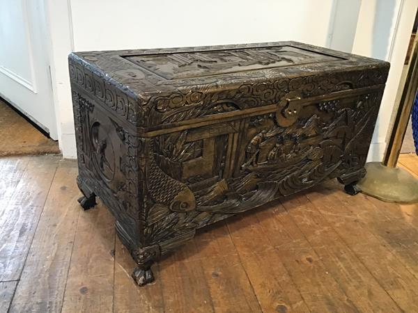 A mid 20thc Hong Kong camphorwood chest, with traditional Chinese scenes carved in relief, on