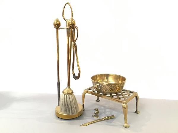 A brass three piece companion stand in the Arts & Crafts style with egg shaped handles and Eastern