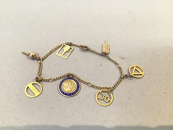 A 9ct gold trace link bracelet mounted with seven 9ct gold road signs (5g) (8cm)