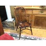 An elm Windsor style spindle back kitchen chair with shaped saddle seat raised on turned splay