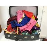 A large collection of saris and other fabrics all within a grey travelling case (72cm x 50cm x