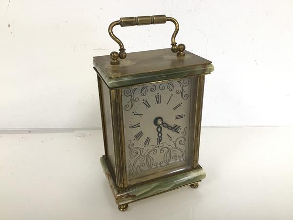 A carriage clock with onyx top and base, with gilt metal mounts, battery movement (16cm including