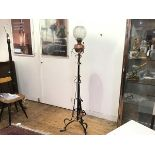 An Arts & Crafts wrought iron copper mounted stylised flowerhead tripod support oil lamp complete