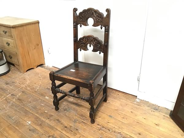 An Edwardian oak carved hall chair with twin relief carved splats and shaped wood seat, raised on
