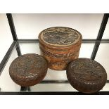 A pair of Japanese wooden circular boxes, each with a carved landscape to lid depicting pagodas, and