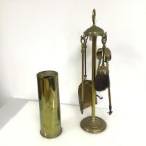 A brass companion set with brush, shovel, tongs and poker (h.55cm), and a 1954 shell casing