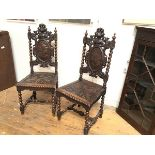 A pair of 19thc oak hall chairs, with surmounted plumed helmet and visor, with oval relief carved