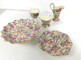 A collection of polychrome floral 1930s china, including milk jug, sugar bowl and footed bowl with