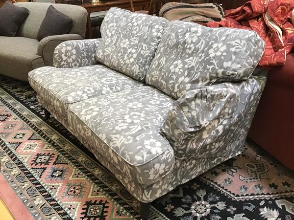 A modern Ikea two seater sofa upholstered in grey and white floral pattern fabric, complete with