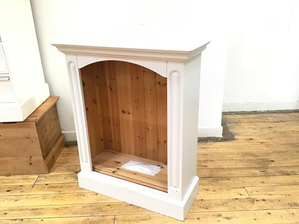 A white painted upright open bookcase with arched top fitted two shelves, on plinth base (98cm x