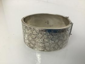 An early 20thc Chester silver bangle with clasp, one side engraved with leaf decoration (3cm x 6cm x