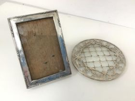 An Edwardian silver photograph frame (16cm x 11cm) and a glass coaster with mounted silver