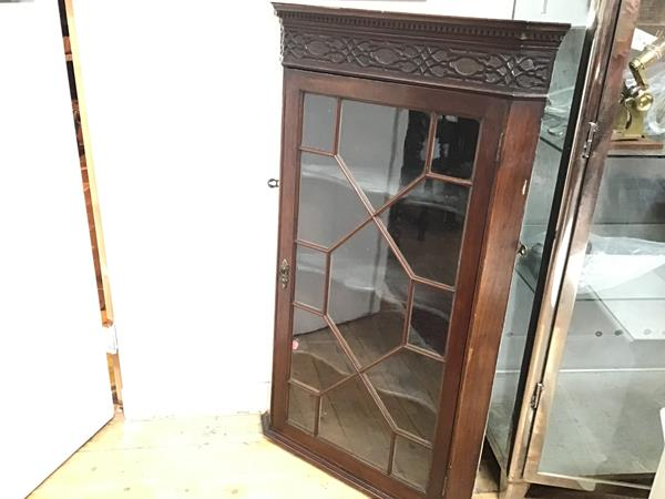 An Edwardian mahogany corner cupboard with blind carved frieze and glazed astragal panel door
