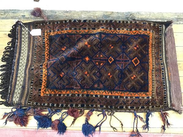 A Kurdish nomadic saddle bag with centre panel of stylised foliate design enclosed within a