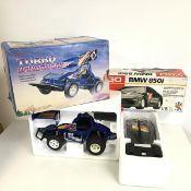 A Radio Shack Turbo wing buggy radio controlled car and a Go BMW radio controlled car, both with