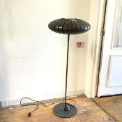 A modern floor lamp, the perforated shade in the form of a flattened Chinese lantern, with