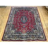 A North-West Persian hand-woven wool carpet, the red field with shaped indigo centre medallion and
