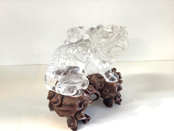A Chinese glass or rock crystal model of a kylin, 20th century, on a carved hardwood stand.