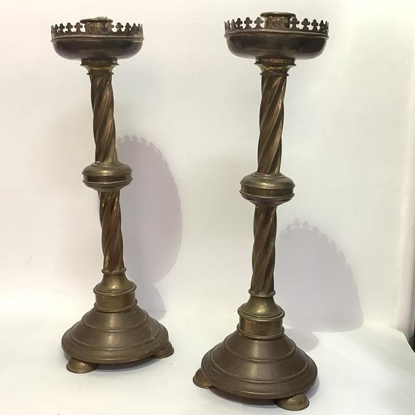 A pair of large Gothic Revival brass altar sticks, 19th century, each candle sconce within a