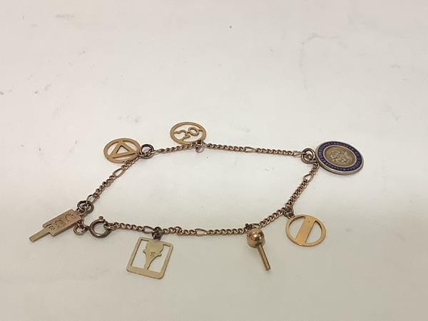 A 9ct gold charm bracelet, of dainty curb links, suspending 9ct gold charms including a blue