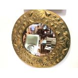 A Scottish Arts & Crafts brass wall mirror, the circular plate within a frame repousse with Celtic