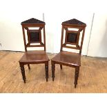 A pair of late Victorian hall chairs, c. 1890, each with pointed pediment with chip-carved