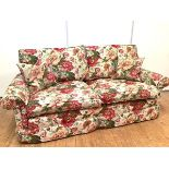 A modern floral upholstered three-seater sofa, with detachable cushion back and seat, between