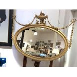 An Edwardian giltwood and gesso wall mirror, the oval plate within a carved egg-and-dart frame
