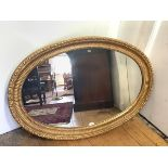 A large oval giltwod wall mirror, the plate within a carved fluted frame incorporating beaded and