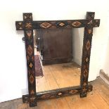 """A 19th/early 20th century """"Tramp Art"""" carved wooden mirror, the rectangular plate within a frame"""