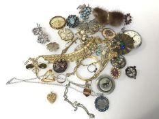 An assortment of costume jewellery including a silver thistle badge, paste and glass brooches, tie