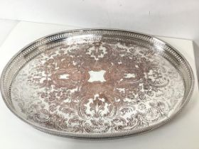 An Epns drinks tray with raised pierced edge and foliate and C scroll decorated top, on squat