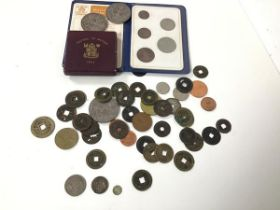A collection of coins including a George III five pence, a small Queen Victoria token inscribed with