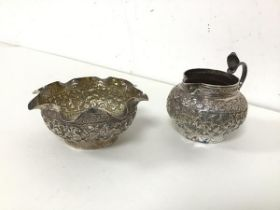 An Indian white metal milk jug and sugar bowl, both with foliate decoration to body, sugar bowl with