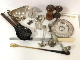 A mixed lot including a white metal candlestick, a bone handled carving knife and stirring spoon,