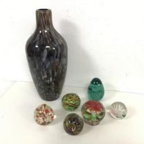 A collection of glass paperweights, some with floral designs, and a Murano style cased glass vase (