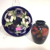 A Moorcroft pottery dish, circular, in the Pansies pattern, against a blue ground, green painted