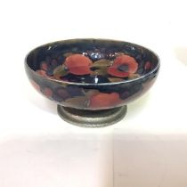 A Tudric Moorcroft pottery bowl, in the Pomegranate pattern, against a shaded blue / green ground,
