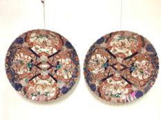A striking pair of large Japanese Imari porcelain chargers, Meiji period, each with scalloped rim