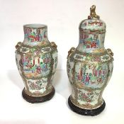 A pair of Chinese porcelain famille rose baluster vases, 19th century, one with domed cover and lion